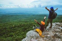 La donna e gli uomini che dell'amante gli asiatici viaggiano si rilassano nella festa La mappa di vista esplora le montagne fotografia stock libera da diritti