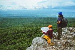 La donna e gli uomini che dell'amante gli asiatici viaggiano si rilassano nella festa La mappa di vista esplora le montagne immagini stock libere da diritti