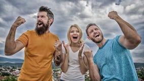 La donna e gli uomini sembrano riuscito emozionale celebrano il fondo del cielo di vittoria Siamo vincitori Celebri il successo c fotografia stock