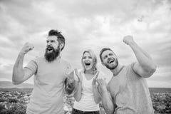 La donna e gli uomini sembrano riuscito emozionale celebrano il fondo del cielo di vittoria Vincitori di trio soddisfatti dei pug fotografia stock libera da diritti