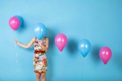 La donna e l'elio balloons su un fondo blu fotografie stock
