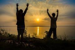 La donna e l'uomo asiatici stanno rinfrescando alzando le armi sulla riva del fiume all'alba o al tramonto Immagine Stock