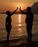 La donna e l'uomo catturano il sole come un cuore Fotografia Stock