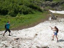 La donna e l'uomo con gli zainhi che stanno di fronte a vicenda ed al gioco aumenta rapidamente sul fondo della neve Fotografia Stock Libera da Diritti