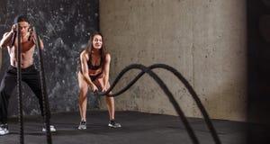 La donna e l'uomo coppia la formazione insieme fare dell'allenamento di combattimento della corda Fotografie Stock Libere da Diritti