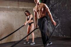 La donna e l'uomo coppia la formazione insieme fare dell'allenamento di combattimento della corda Fotografia Stock Libera da Diritti