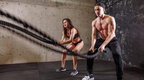 La donna e l'uomo coppia la formazione insieme fare dell'allenamento di combattimento della corda Immagini Stock Libere da Diritti
