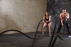 La donna e l'uomo coppia la formazione insieme fare dell'allenamento di combattimento della corda Fotografia Stock