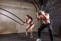 La donna e l'uomo coppia la formazione insieme fare dell'allenamento di combattimento della corda Immagine Stock