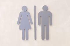 La donna e l'uomo grigi firmano sulla parete Immagini Stock
