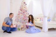 La donna e l'uomo passano a regali di Natale la sua metà in bedro spazioso Immagine Stock