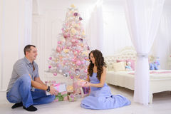 La donna e l'uomo passano a regali di Natale la sua metà in bedro spazioso Fotografia Stock Libera da Diritti