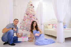 La donna e l'uomo passano a regali di Natale la sua metà in bedro spazioso Fotografia Stock