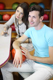 La donna e l'uomo si siedono alla tabella nel randello di bowling Immagini Stock Libere da Diritti