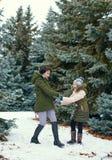 La donna e la ragazza stanno giocando con le palle di neve nella foresta dell'inverno, bello paesaggio con gli abeti nevosi fotografia stock