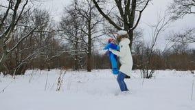 La donna ed il bambino che giocano nell'inverno parcheggiano stock footage
