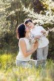 La donna ed il bambino felici nella fioritura fanno il giardinaggio immagini stock