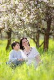 La donna ed il bambino felici nella mela di primavera fanno il giardinaggio Fotografie Stock Libere da Diritti