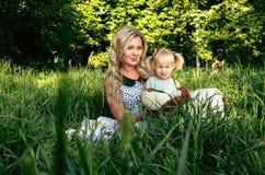 La donna ed il bambino felici nella molla di fioritura fanno il giardinaggio Concetto di festa di giorno di madri o del giorno de immagine stock
