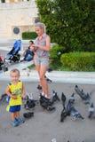La donna ed il bambino giocano con i piccioni - Atene, Grecia Fotografia Stock