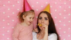 La donna ed il bambino soffiano i corni, sorridenti e ridenti Madre e corno di salto e divertiresi della figlia Buon compleanno stock footage
