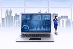 La donna ed il grafico sul computer portatile celebrano il suo risultato Fotografia Stock