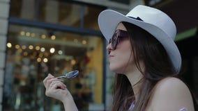 La donna elegante gode di di mangiare la confetteria dolce in caffè della via archivi video