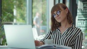 La donna elegante sta bevendo il caffè, guardante il video sullo schermo del computer portatile stock footage