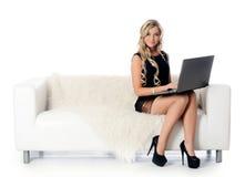 La donna elegante su un sofà bianco con il computer portatile. Affare concentrato Immagine Stock Libera da Diritti