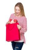 La donna elimina il contenitore di regalo dal sacchetto della spesa Fotografie Stock Libere da Diritti