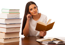 La donna emozionante ha concentrato la lettura dietro la tavola con il mucchio di Fotografie Stock Libere da Diritti