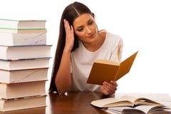 La donna emozionante ha concentrato la lettura dietro la tavola con il mucchio di Fotografia Stock Libera da Diritti