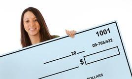 La donna emozionante ostacola l'assegno bancario in bianco gigante Fotografie Stock
