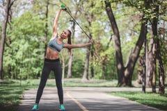 La donna energetica sta esercitandosi con il salto della corda fuori Fotografie Stock