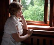 La donna esamina dalla finestra un legno Fotografia Stock Libera da Diritti