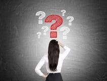 La donna esamina i punti interrogativi sulla lavagna Fotografia Stock