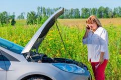La donna esamina il motore e parla sul telefono Immagine Stock