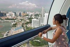 La donna esamina la città dal cabine della ruota panoramica Immagini Stock Libere da Diritti