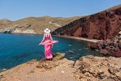 La donna esamina la spiaggia rossa in Santorini, Grecia fotografia stock