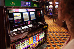 La donna esamina le slot machine la fodera Fotografie Stock