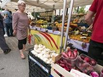 La donna esamina le verdure sul mercato dell'aria aperta di briancon nell'Alta Provenza francese Immagine Stock