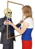 La donna esamina lo scheletro come riflessa Fotografie Stock