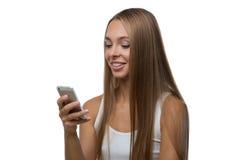 La donna esamina lo schermo dello smartphone e sorride Immagine Stock