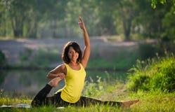 La donna esegue gli esercizi e Pilates di yoga in natura Fotografia Stock