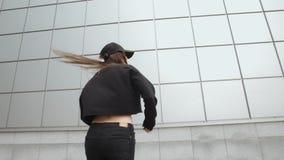 La donna esegue il ballo hip-hop moderno contro stile libero contemporaneo della parete del metallo, environmen urbani video d archivio