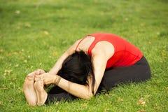 La donna esegue la curvatura di andata profonda in parco Fotografia Stock Libera da Diritti