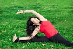 La donna esegue la curvatura laterale in parco Immagini Stock