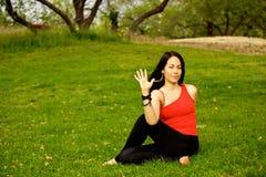 La donna esegue la torsione obliqua di seduta in parco Fotografie Stock Libere da Diritti