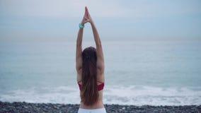 La donna esile è mani aumentanti su e considerando il mare all'aperto, praticando l'yoga stock footage