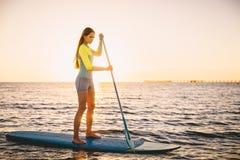 La donna esile perfetta sta sulla pagaia che pratica il surfing nell'oceano con i bei colori del tramonto immagini stock libere da diritti